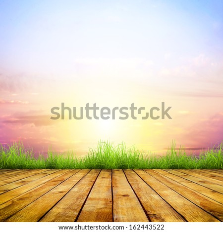 Fresh spring green grass with nice sky sunlight and wood floor. Beauty natural background - stock photo