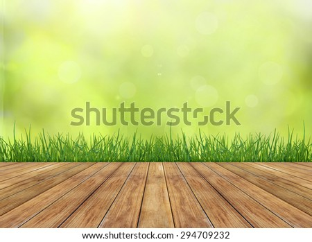 Fresh spring green grass with sunlight background from tree and wooden floor