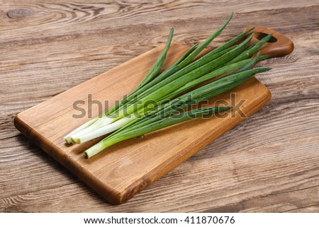fresh spring green onions on a cutting board kitchen. - stock photo