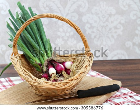 Fresh spring onions in a basket with copy space. - stock photo