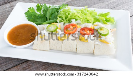 Fresh spring rolls, vegetables wrapped in dough, topped with mustard, crab meat and chili, eaten with sauce, on white plate, place on wooden background