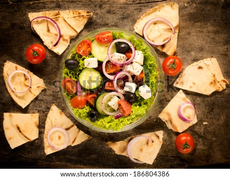 Fresh spring salad in bowl and tortilla bread from above on wooden background - stock photo
