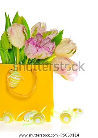 fresh spring tulips in yellow bag with easter eggs decoration over white background - stock photo