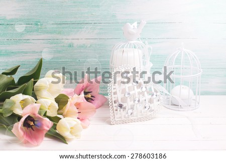 Fresh  spring white and pink tulips flowers,  decorative heart and candles in ray of light  on white  painted wooden planks against turquoise wall. Selective focus.  - stock photo