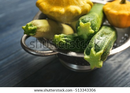 Fresh squashes and zucchini in stainless colander on blue wooden background