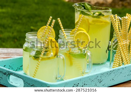 Fresh squeezed lemonade in mason jar mugs and glass pitcher sitting on blue weathered drink tray with yellow straws and fresh lemon slices - stock photo