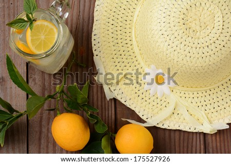Fresh Squeezed Lemonade on a rustic wooden table with lemons and a yellow sun hat. Horizontal format with an oldtime feel, shot from a high angle. - stock photo