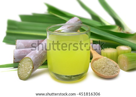 Fresh squeezed sugar cane juice in clear glass with cut pieces cane and brown sugar on white background.