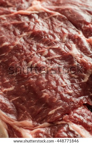 Fresh steak on marble background. Uncooked beefsteak cooking on a kitchen. Delicious, spicy, juicy meat with copy space closeup. - stock photo