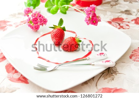 Fresh strawberries  as romantic dessert  on a plate in heart shape of berry sauce. selective focus