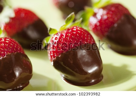 fresh strawberries dipped in dark chocolate - stock photo