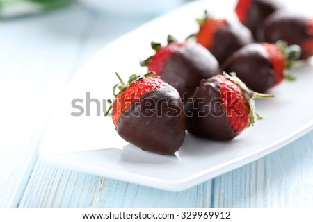 Fresh strawberries dipped in dark chocolate on blue wooden background - stock photo