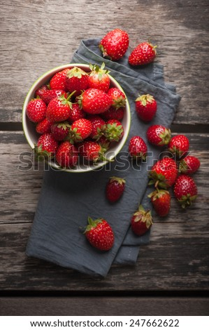 Fresh strawberries from farm on wood table with low key scene. - stock photo