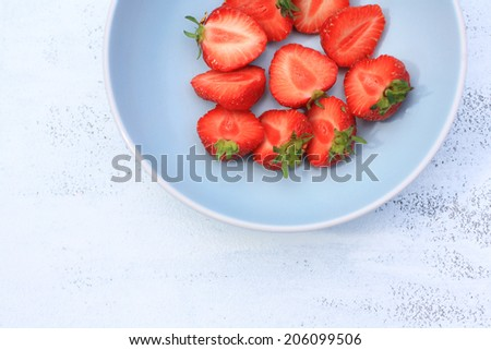 Fresh strawberries in a blue bowl, close up - stock photo