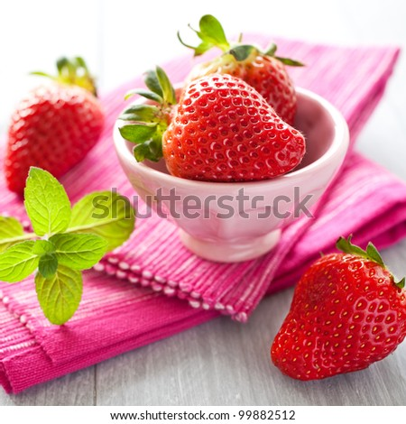 fresh strawberries in a  bowl with mint - stock photo