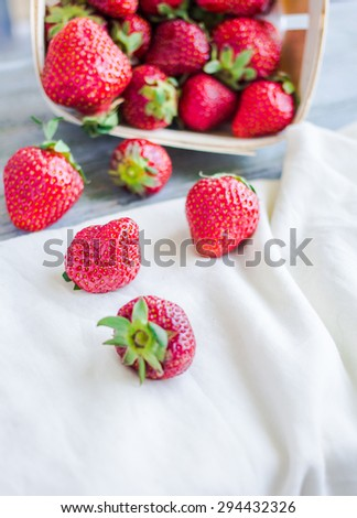 fresh strawberries in a box on a blue wooden board, raw food, summer berries, selective focus
