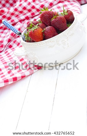 Fresh strawberries in a white bowl on a white wooden background