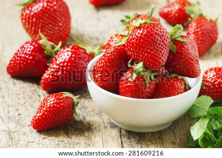Fresh strawberries in a white porcelain bowl on wooden table in rustic style, selective focus - stock photo