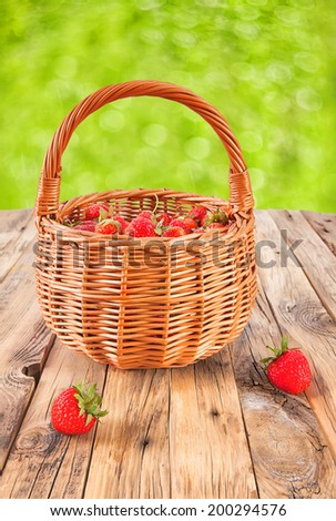 fresh strawberries in a wicker basket on a wooden table on a white background