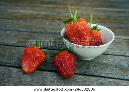 Fresh strawberries in bowl on wooden table - stock photo
