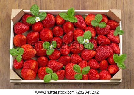 fresh strawberries in wooden box isolated on table - stock photo