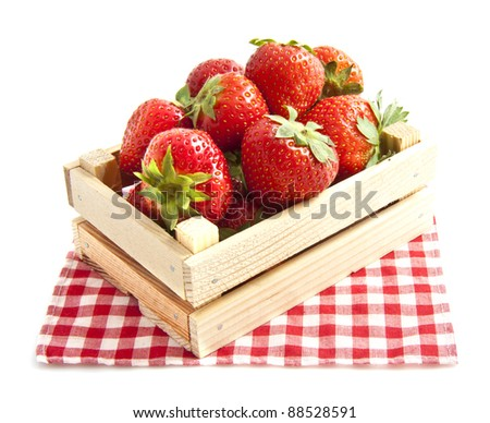Fresh strawberries in wooden box on red white chequered napkin over white - stock photo