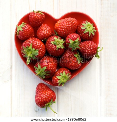 Fresh strawberries on a plate in the shape of heart - stock photo