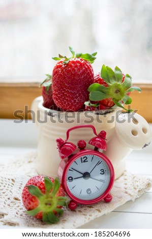 Fresh strawberries on the table and old-styled red clock - stock photo