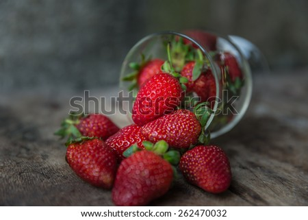 Fresh strawberries spilled from a glass-Still Life - stock photo