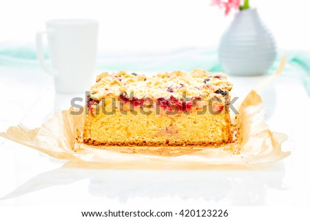 Fresh strawberry and raspberry sponge cake with vanilla crumble on white table with vase with Flowers. Fruits Greek Yogurt Cake. Picnic for a summer vacation with perfect cake.