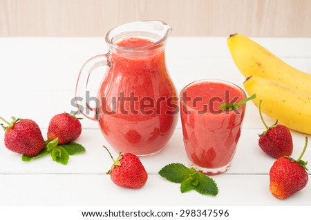 Fresh strawberry banana smoothie with mint on a white wooden background. Healthy foods. Selective focus