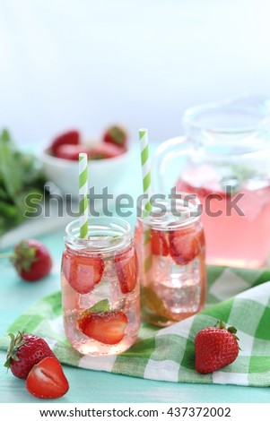 Fresh strawberry drink in bottle on wooden table - stock photo