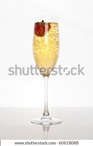 fresh strawberry floating in glass of champagne - stock photo