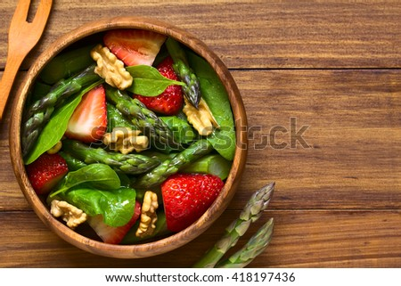 Fresh strawberry, green asparagus, baby spinach and walnut salad served in wooden bowl, photographed overhead on dark wood with natural light (Selective Focus, Focus on the top of the salad)