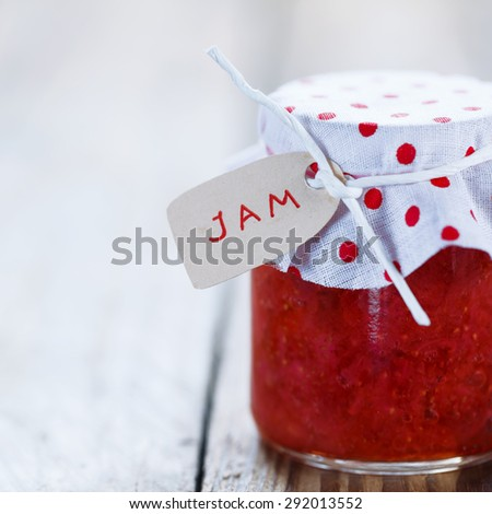 Fresh strawberry homemade jam in jar on white wood background. healthy organic and vegan food. - stock photo