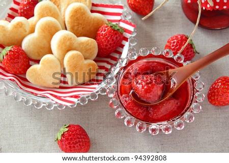Fresh strawberry jam with heart shaped toast - stock photo