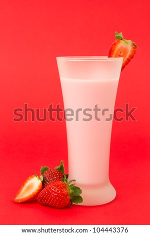 Fresh strawberry yogurt drink surrounded by strawberries