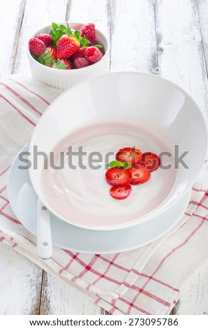 Fresh strawberry yogurt in a bowl with fresh berries