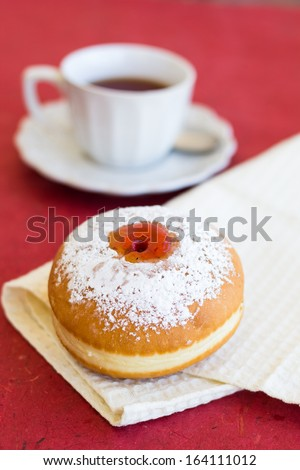 Fresh sufgniya (donut) on a napkin with a cup of tea - stock photo