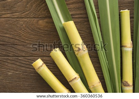 Fresh sugarcane cut into pieces on a wooden table with leaves and cane, top view. - stock photo