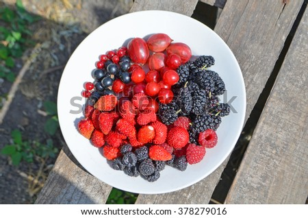 Fresh summer berries on plate. Top view. Rustic style. - stock photo