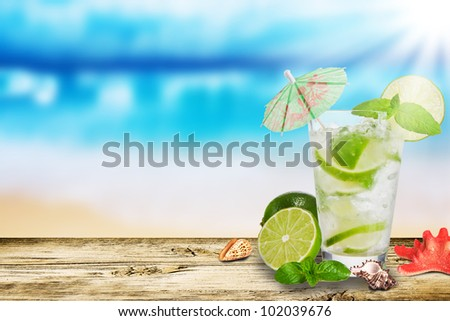 Fresh summer cocktail on wooden table. Blur beach on background - stock photo
