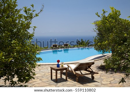Fresh summer drink placed and sunbed next to swimming pool with mediterranean on background.
