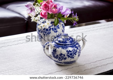 Fresh summer flowers in an oriental style blue and white china ginger jar on a table with a matching sugar basin as a centrepiece to a tea table - stock photo