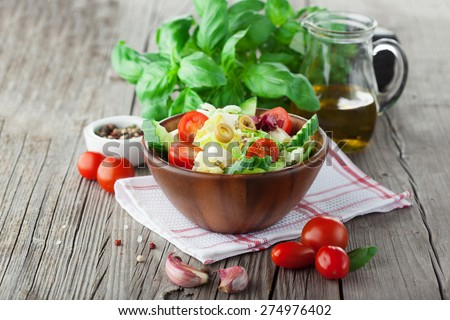 Fresh summer salad with cherry tomatoes, spinach, arugula, romaine and lettuce on dark wooden background, selective focus - stock photo