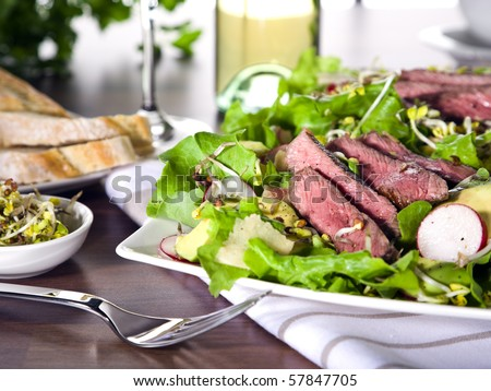 fresh summer salad with stripes of fried beef on avocado slices with sprouts, radish and ginger