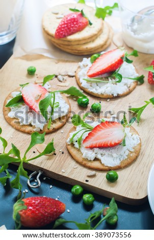 Fresh Summer Snack Crisp Cookies Cottage Cheese Strawberry Seeds Peas Almond Flakes Summer Fruits Vegetables on Chopping Board - stock photo