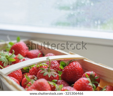 Fresh summer strawberries in wooden basket against the rainy window with drops of rain. Closeup with extremely shallow DOF. - stock photo