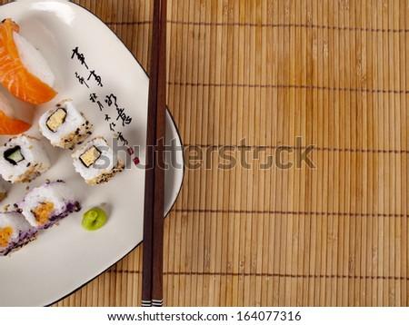 Fresh sushi and sashimi on a plate with chopsticks - stock photo