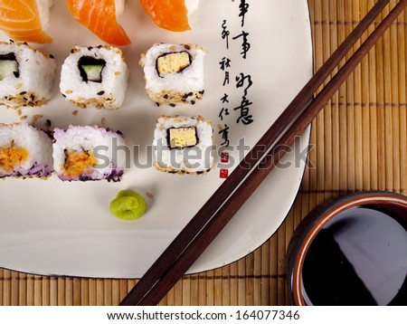 Fresh sushi and sashimi on a plate with chopsticks and soy sauce - stock photo